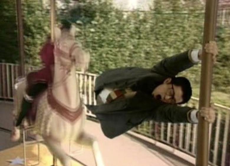 十年愛で大江千里が高速で回るメリーゴーランドにつかまっている写真