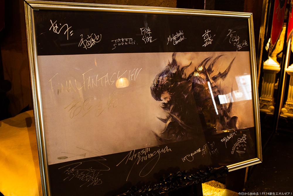 竜騎士のアートに開発陣のサインが書き込まれている。エオルゼアカフェ、横浜店にて撮影。(FF14)