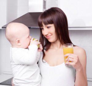 ラルフィンガードルで痩せ、赤ちゃんを見つめながらジュースを持つ女性