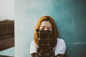 イージースリムレッグでスタイルアップした長袖で口を覆う女性