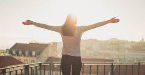 クリスチャンココで体型が変化し、両手を広げ夕日と共に幸せを感じる女性