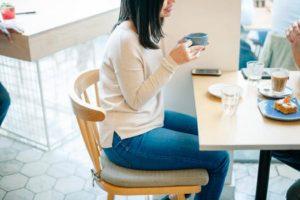 椅子に座る猫背のビットシェイパー(Bitshaper)愛飲女性