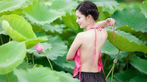 緑の大きい葉と、ピンクの花に囲まれ、嬉しそうな笑顔の横顔を見せている、背中が綺麗な細身の女性の写真。