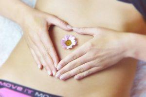 おへそに可愛い花を添え、手でハートを描いている、女性の細いウエストの写真。