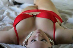 赤い下着を着てベッドに横になっている、スタイルの良い女性の写真。