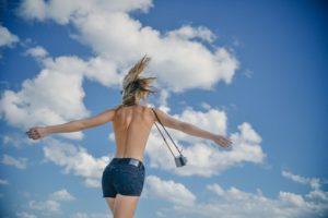 青空の下でカメラを持ち嬉しそうにはしゃいでいる、美しい背中の女性写真。