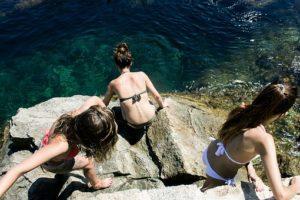 痩せて綺麗な体型をしている3人の女性が、夏にビキニを着て、海水浴を楽しんでいる風景の写真。