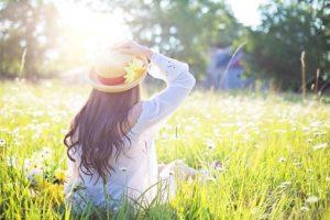 草むらに座る帽子をかぶった幸せそうな女性