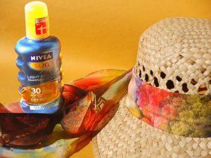 日焼け止めクリームと麦わら帽子の写真