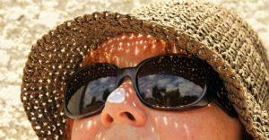 サングラスをし、鼻先に日焼け止めクリームをのせている女性の写真