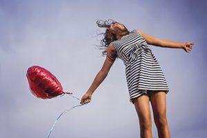 空をバックに、赤いハートの風船を持ち、嬉しそうに飛び跳ねている、スリムな体の女性写真。