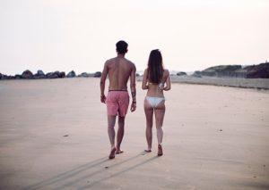 水着を着て、砂浜を歩く、健康でスタイルの良い男女の後ろ姿の写真。