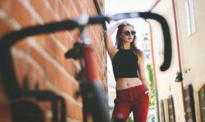 自転車のハンドルを前に、遠くでサングラスをかけ、ポーズを撮っているスタイルの良い女性の写真。