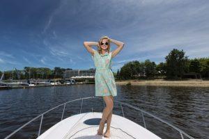 船の上で、華やかなワンピースを着て、笑顔でポーズをとっている、スリムで美しい女性の写真。