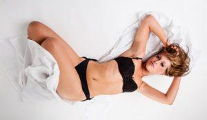 白いベッドの上で、黒の下着を着て、カメラ目線でポーズを決めている、ブロンド髪の細くスタイルの良い女性の写真。