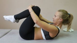 黒いレギンスを履いている女性が、両手で膝をつかみ、寝ながらストレッチをしている写真。