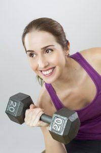 バーベルを持ち、にこやかにトレーニングを行なっている女性の写真。