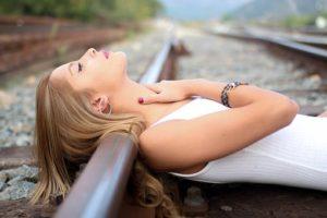 白い服を着て線路で寝転び、首元に手をあてている、色白で美しいお肌をした女性の写真。