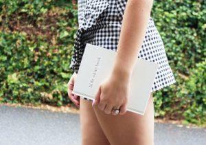 片手に白い本を持ち、自然の中を散歩している女性のウエストから、太ももにかけての写真。