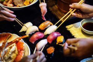 5名でテーブルを囲み、美味しそうなお寿司にお箸を差し伸べている写真。
