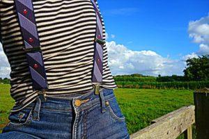 緑や青空が見える綺麗な景色を背景に、ボーダーのシャツを着て、サスペンダーをしジーンズを履いている、ウエストが細く、服を綺麗に着こなすことができている人の胸元から、ウエストまでの写真。