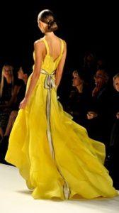 多くの女性が憧れるような美しいスタイルをしているモデルが、黄色のドレスを着てファッションショーの舞台で歩いている写真。