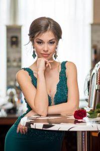 胸元が開いているグリーンのドレスを着て、グリーンのピアスをし、レストランのテーブルにひじをつき、手に顎をのせポーズをとっている、細く美しく、セクシーな女性の写真。