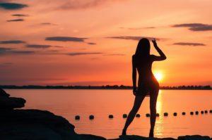 オレンジ色の夕日が綺麗な海を背景に、ボディーラインが美しくスタイルの良い女性が、ピースサインでポーズをとっている写真。