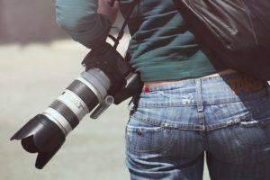緑のロングTシャツに、ジーンズを履いている、小さく引き締ったお尻をしている女性が、肩からカメラをかけて歩いている後ろ姿の写真。