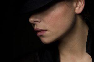 黒を背景に、黒い帽子を被り、目元を隠している、ツヤのある綺麗な肌をした女性の横顔写真。