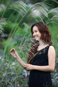 黒いワンピースを着ている、肌が白く綺麗な女性が、自然の中で幸せそうに微笑んでいる写真。