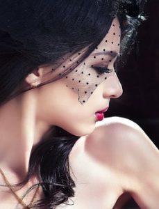 頭部から頬にかけて、ドット柄のレースを被り、目線を斜め下に向けている、黒髪で色白の美しい女性の横顔写真。