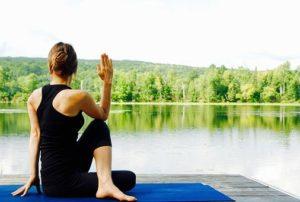 湖と山、大自然を背景に、健康的でスタイルが良い女性がヨガマットを敷き、ストレッチをしている様子の写真。
