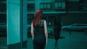 街のビルのガラスに映る自分自信のスリムで美しい体型にうっとりしているかのように、ポーズをして立っている、黒いタイトなワンピースを着た美しい女性の写真。