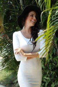 タイトな白のワンピースを着ている、スタイルの良い女性が、自然の中で腕を組み、幸せそうに微笑んでいる様子の写真。