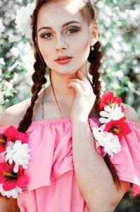 ピンクの服を着て、左手で首もと触れてポーズをとっている、三つ編みロングへアの、美肌の美しい女性の写真。