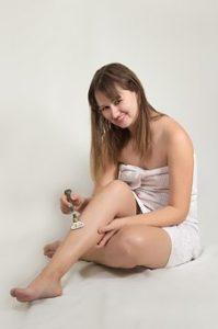 体に一枚のタオルを巻いている女性が、にこやかにカメラ目線で除毛をしている様子をとっている写真。