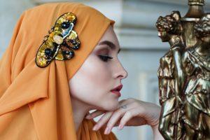オレンジ系のターバンを頭に巻いて、左手を顎に添えて、視線を下へ落としてポーズをとっている、美白、美肌の美しい女性の写真。