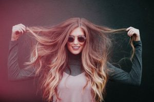 サングラスをかけているオシャレな女性が、美しいロングの髪の毛を両手で広げ、カメラに向かい笑顔でポーズをとっている写真。