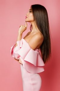 薄いピンクのフリルワンピースを着ていて、艶のある綺麗な肌をした女性が、顎に人差し指を付けてポーズをとっている写真。