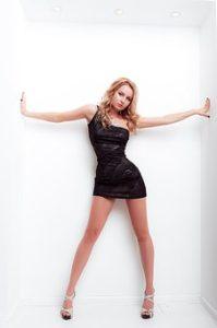 白い壁をバッグに、脚が細長く、曲線がとても美しい体をしているセクシーな女性が、体にフィットしている黒いワンピースを着て、ポーズをとっている写真。