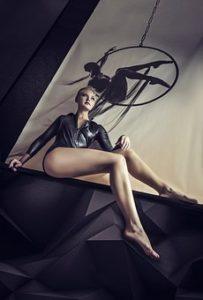 長くてメリハリのある美しい脚をしている女性が、座ってポーズをとっている写真。
