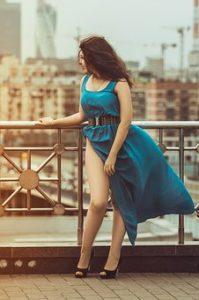 ターコイズブルーのワンピースを着ている、美脚女性の写真。