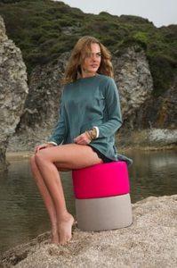 川辺で座っている、美脚女性の写真。