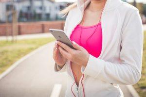 カジュアルなスポーツウェアを着て、携帯を確認している女性の写真