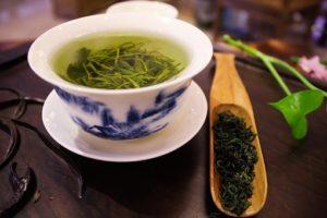 コップ一杯の緑茶と緑茶の葉