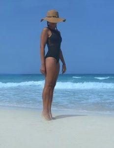 麦わら帽子を被り、水着を着ているスタイルの良い女性が、砂浜で爪先立ちをしている写真