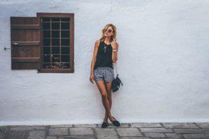 短パン、ノースリーブ姿でサングラスをかけている、スタイルの良いオシャレな女性