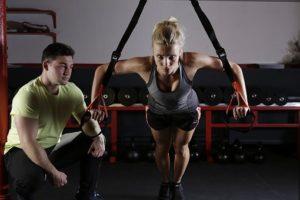 トレーニングをしている女性と、横で指導している男性の写真