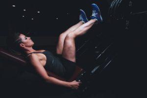 ジムで足の筋肉トレーニングをしている女性の写真